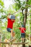 2 милых дет, братья мальчика, взбираясь в спортивной площадке s веревочки Стоковое фото RF