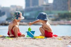 2 милых дет, играя в песке на пляже Стоковые Изображения RF