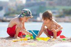 2 милых дет, играя в песке на пляже Стоковая Фотография RF