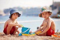 2 милых дет, играя в песке на пляже Стоковая Фотография