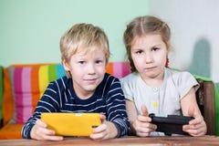 2 милых дет с smartphones в руках смотря камеру Стоковая Фотография