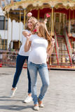 2 милых женщины в парке атракционов имея потеху и есть помадки, счастливую семью Samesex лесбосская семья, беременная пара Стоковые Фото
