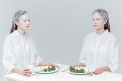 2 милых женщины моды есть на таблице Стоковое Фото