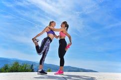 2 милых женщины протягивая в парке перед начинать встречу разминки стоковая фотография rf