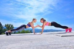 2 милых женщины протягивая в парке перед начинать встречу разминки Стоковое Изображение RF