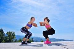 2 милых женщины протягивая в парке перед начинать встречу разминки Стоковое Фото