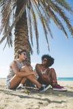 2 милых женщины сидя на смеяться над пляжа Стоковое Изображение RF