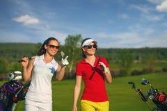 2 милых игрока в гольф женщин идя на поле для гольфа Стоковое фото RF