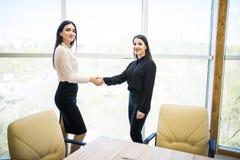 2 милых коммерсантки тряся руки в современном офисе Стоковые Изображения RF