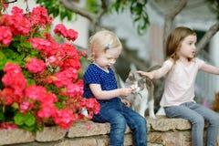 2 милых маленьких сестры и кот Стоковая Фотография