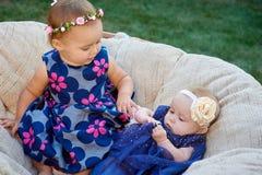 2 милых маленьких сестры смеясь над и играя на стуле в зеленом солнечном парке Стоковое фото RF