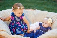 2 милых маленьких сестры смеясь над и играя на стуле в зеленом солнечном парке Стоковые Изображения