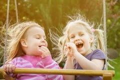 2 милых маленькой девочки имея потеху на качании совместно в beautifu Стоковые Изображения