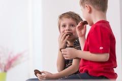 2 милых мальчика сидя на кресле Стоковое Изображение