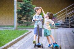 2 милых мальчика, состязаются в самокатах катания, внешних в парке, летнем времени Стоковые Изображения