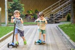 2 милых мальчика, состязаются в самокатах катания, внешних в парке, летнем времени Стоковые Фотографии RF