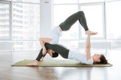 2 милых молодой женщины делая йогу acro Стоковое Изображение