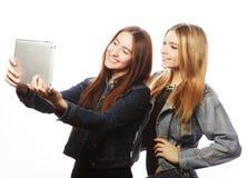 2 милых молодой женщины принимая автопортрет с таблеткой Стоковые Фото