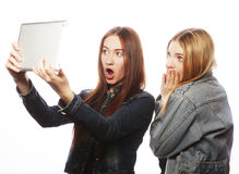 2 милых молодой женщины принимая автопортрет с таблеткой Стоковая Фотография RF