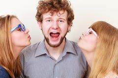 2 милых молодой женщины целуя красивого человека Стоковая Фотография