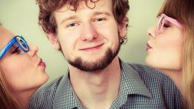 2 милых молодой женщины целуя красивого человека Стоковые Изображения