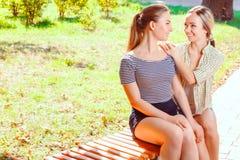 2 милых подруги сидя в парке Стоковые Изображения RF
