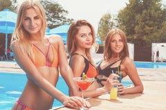 3 милых подруги с коктеилями на бассейне Стоковое Изображение RF