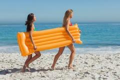 2 милых друз бежать держащ тюфяк воздуха Стоковые Изображения RF