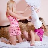 2 милых сестры воюя подушки на кровати Стоковая Фотография