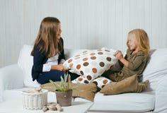 2 милых сестры дома играя, маленькая девочка в интерьере дома на софе, messing волосы, воюя с подушками, образ жизни Стоковые Фото