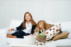 2 милых сестры дома играя, маленькая девочка в интерьере дома Стоковые Изображения RF