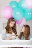 2 милых сестры с именниным пирогом и воздушными шарами Стоковое фото RF