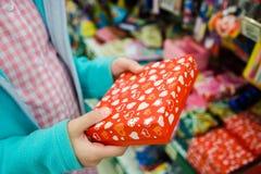 Младенец вручает держать красную подарочную коробку с сердцами, подарок упаковывая в руках покупателя стоковые фотографии rf