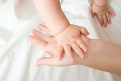 младенец вручает мать малую Стоковые Фотографии RF