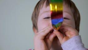 Младенец в благородном настроении Счастливый ребенок играя с праздничным язык-свистком Счастливая предпосылка детства Искусство и акции видеоматериалы