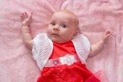 Младенец в платье, красивый ребенок лежа на кровати в платье стоковое фото rf