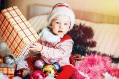 Младенец в рождестве шляпы гнома раскрывая его подарок на рождество стоковое изображение