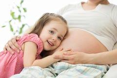 Младенец девушки маленького ребенка слушая в животе ее мамы Беременность и новые концепции жизни Стоковые Фотографии RF