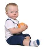 младенец держа померанцовое усаживание стоковое изображение