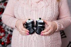 младенец держа супоросую женщину ботинок стоковые изображения