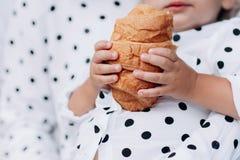 Младенец держит круассан в его руке удержание очень вкусного круассана с золотой коркой стоковые изображения rf