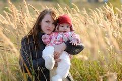 младенец ее детеныши мати лужка удерживания Стоковая Фотография RF