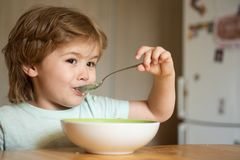 Младенец есть еду на кухне r Милый ребенк ест Немногое младенец ест Мальчик имея завтрак внутри стоковая фотография rf