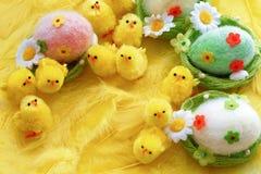 Младенец желтая пасха забавляется цыпленоки и яичка на предпосылке feath Стоковые Фотографии RF