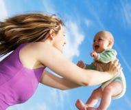 младенец задерживая детенышей женщины Стоковая Фотография RF