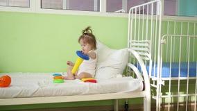 Младенец играет на кровати с пирамидой и покрашенными кольцами Воспитательные игрушки для детей preschool и детского сада Игрушка акции видеоматериалы