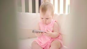 Младенец играя с smartphone Шарж девушки ребенк наблюдая на черни сток-видео