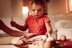 Младенец имея потеху крася пасхальные яйца Стоковая Фотография