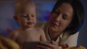Младенец как раз сидя на неудаче с его матерью и она показывают ему мультфильм с ее телефоном с камерой подачи видеоматериал