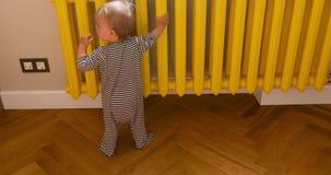 Младенец касаясь батарее дома сток-видео